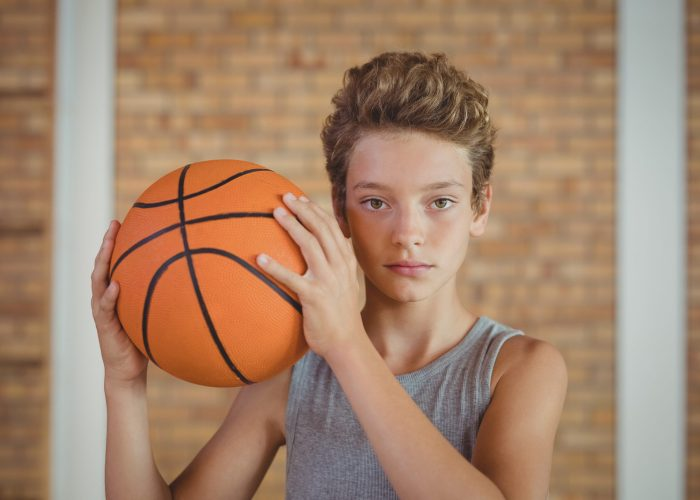 Determined boy holding a basketball in the court