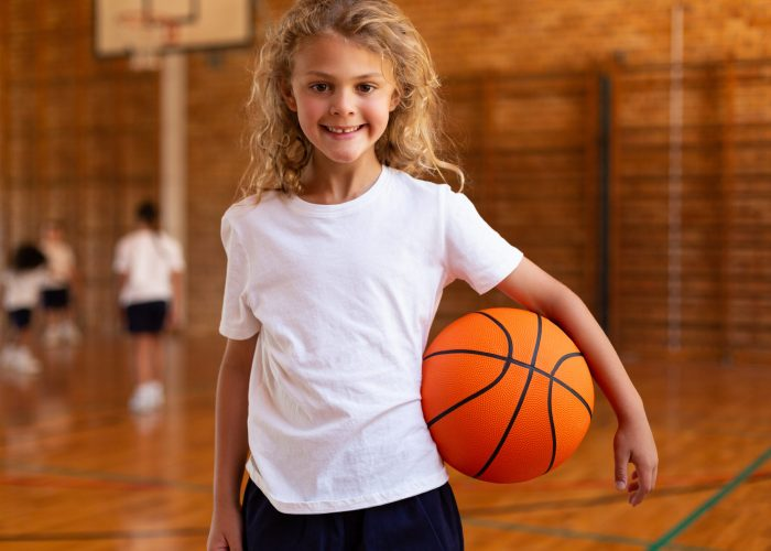 Front view of a mixed -race happy schoolgirl holding a basketball and looking at the camera in a basketball court